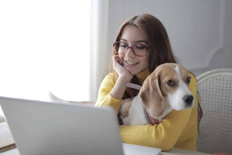 Frau sitzt mit Hund vor dem Laptop