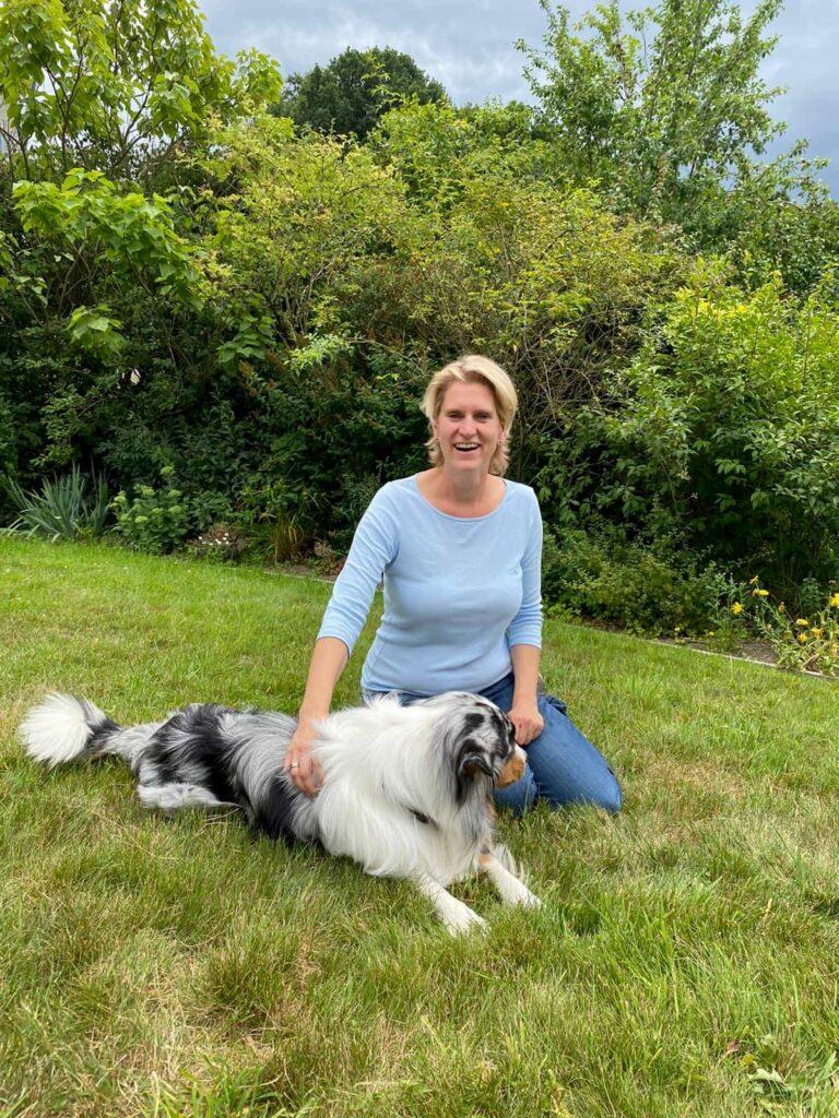 Dr. Kathrin Kirschbaum sitzt neben einem Hund auf einer Wiese