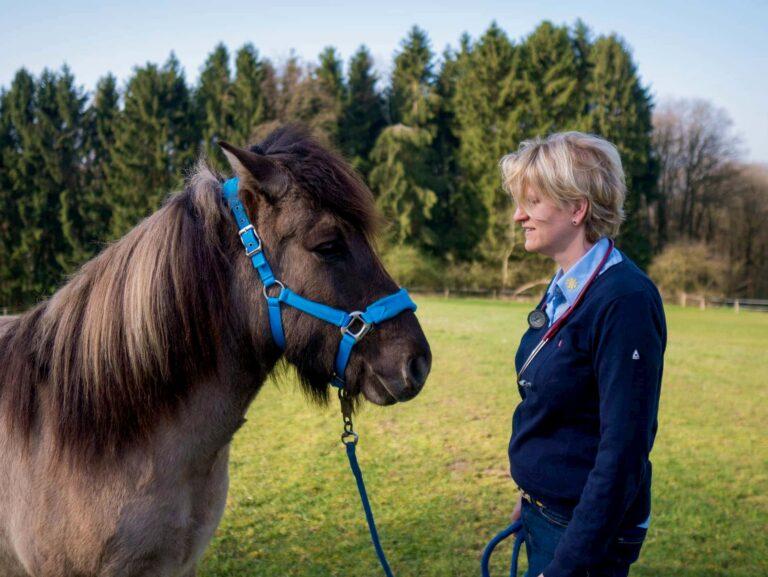 Dr. Kathrin Kirschbaum steht auf einer Wiese mit ihrem Pferd